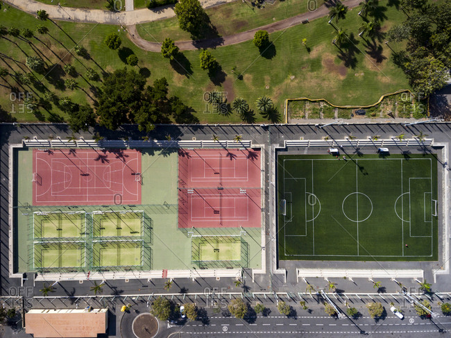 Aerial view over sports park in the city with basketball and tennis courts
