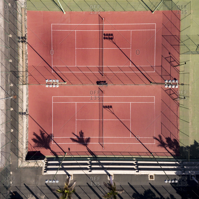 Overhead view of red tennis courts in the city