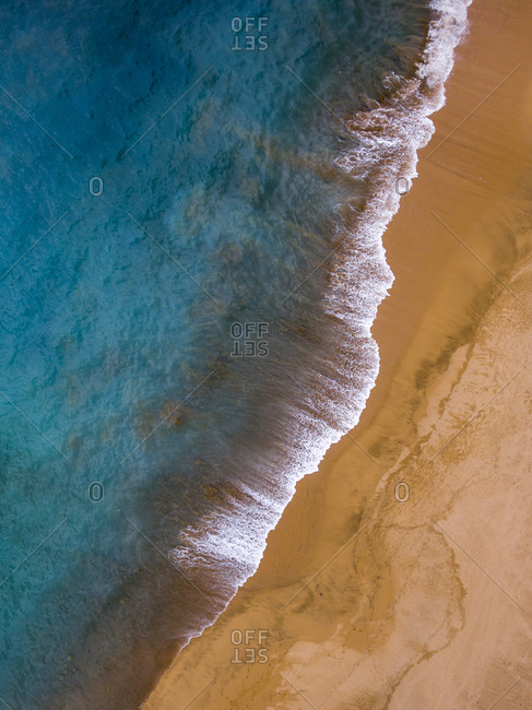Aerial view of the waves rolling into an empty beach by the ocean