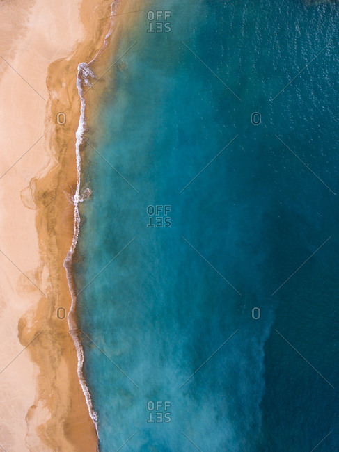 Aerial view of the empty beach by the turquoise ocean