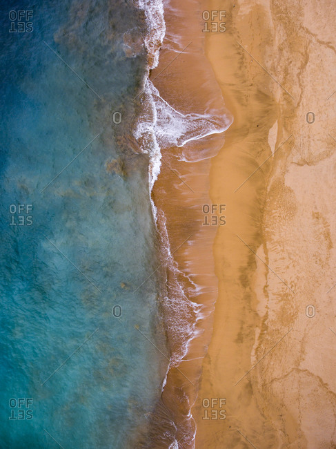 Bird's eye view of the empty beach by the turquoise ocean