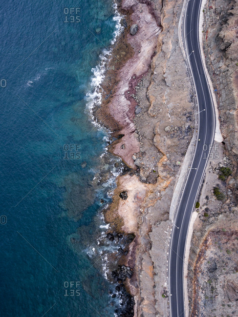 Aerial view over a winding coastal road by the ocean