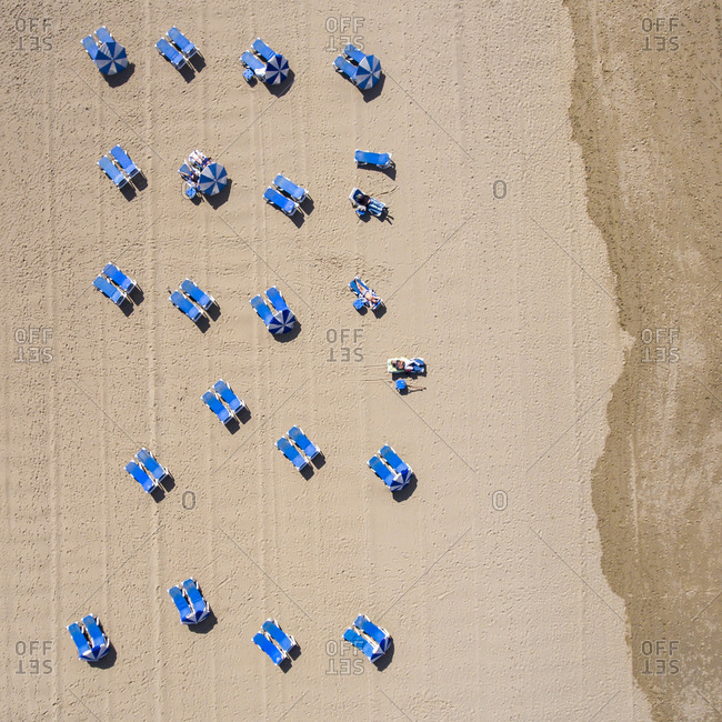Beach with blue lounge chairs and umbrellas from the bird's eye view