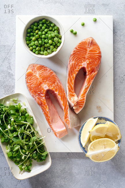 Raw salmon steak top view with micro greens, lemon and green peas. Ingredients for cooking healthy dinner.