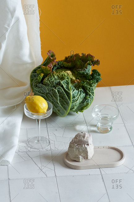 Still life with savoy cabbage, lemon and tiles on yellow background