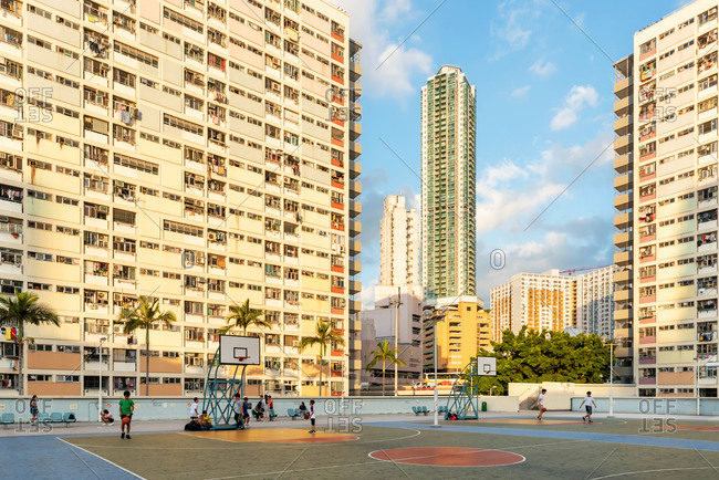 May 16, 2018: Kids playing basketball in front of some Colorful facades of public housing complexes in Hong Kong