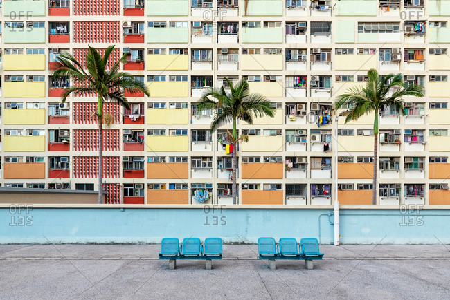 Some benches in front of colorful facades of public housing complexes in Hong Kong