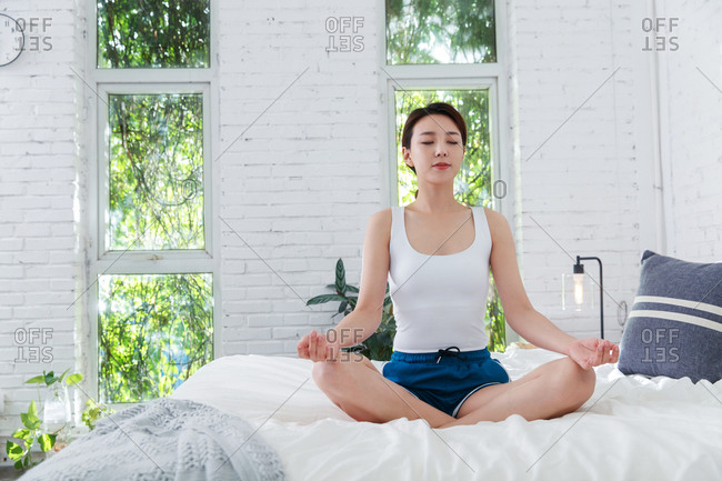 Young woman meditating on her bed