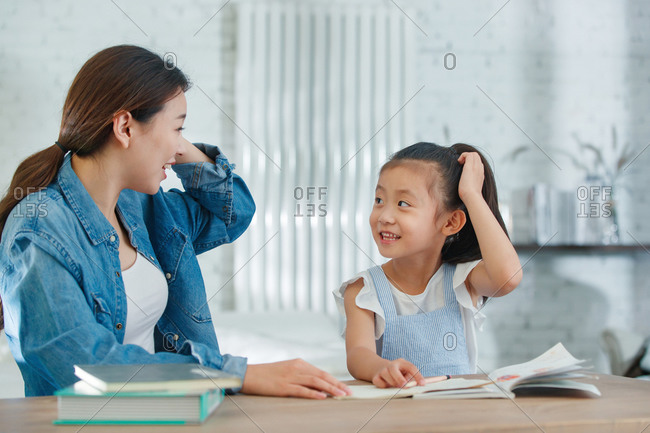 Mom helping daughter with her homework at home
