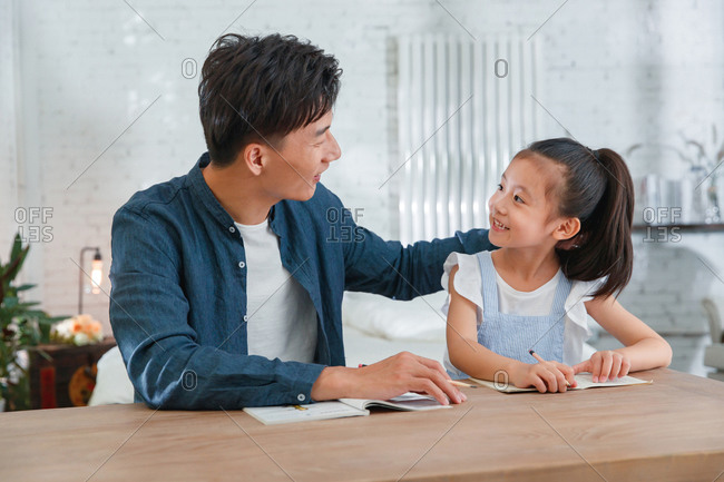 Young dad helping his daughter with her homework