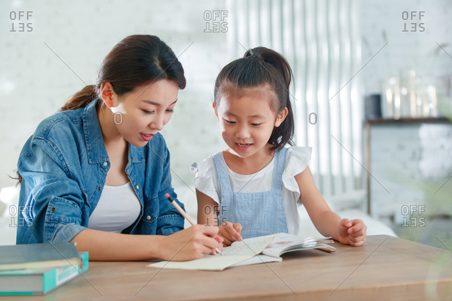 Young mom helping her daughter with her homework