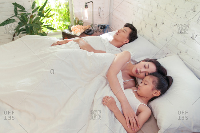 Family of three sleeping together at home