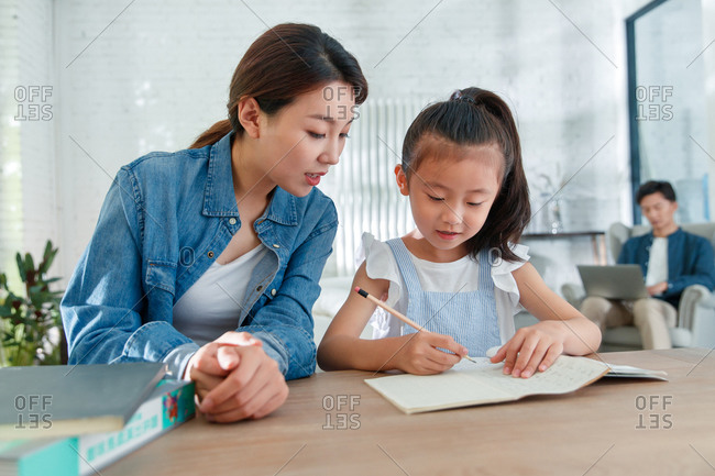 Mom helping daughter with her homework while dad works from home