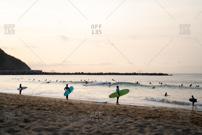 Three separated surfers standing on the shore of a beach during sunset while lots of surfers are surfing