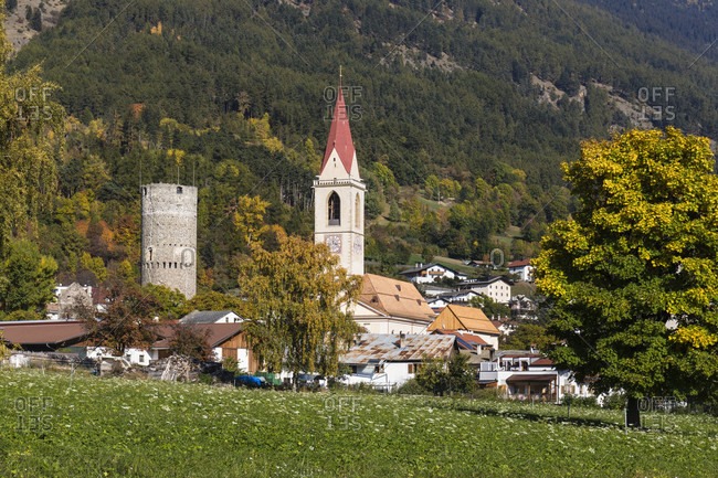 October 20, 2017: Round tower of the keep of the former Frohlich castle from the 13th century and church tower of the parish church of the Assumption, Mals, Vinschgau, Bolzano province