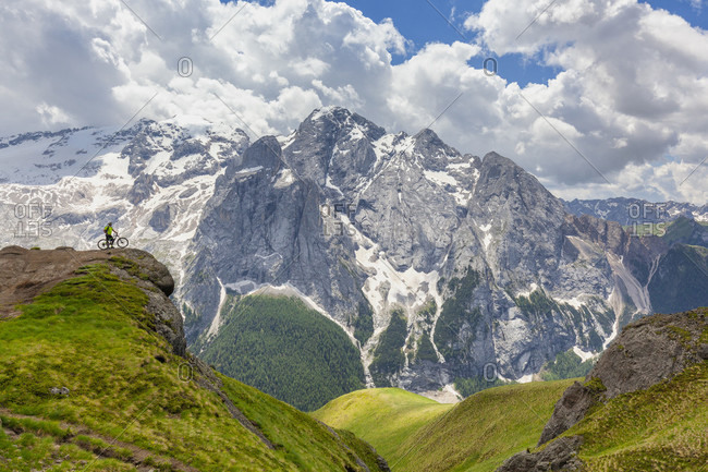 June 21, 2020: Cyclist with an electric mountain bike (e-bike) along the trail Viel del Pan (Bindelweg) in front of Marmolada, Padon ridge on the borders between Veneto and Trentino Alto Adige Italy