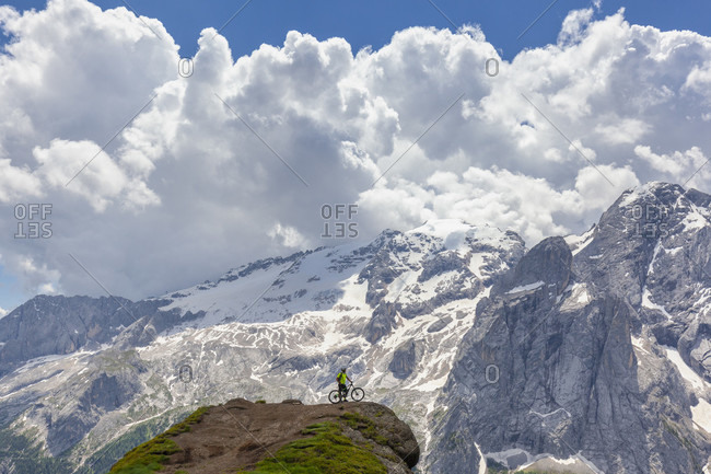 Cyclist with an electric mountain bike (e-bike) along the trail Viel del Pan (Bindelweg) in front of the Marmolada, Padon ridge on the borders between Veneto and Trentino Alto Adige Dolomites, Italy