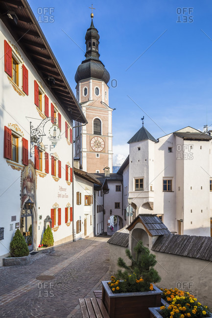 July 14, 2018: Alley with the facade of the Turmwirt and the bell tower of the parish church of Saints Peter and Paul, Castelrotto, Bolzano province, Trentino-South Tyrol, Italy