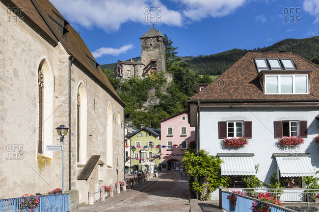 July 17, 2018: Old town houses and parish church St. Andreas with the Burghauptmannsturm in the background, Klausen, Eisacktal, Bolzano province, Trentino-South Tyrol, Italy