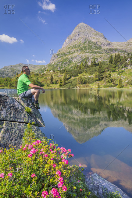 Colbricon lakes in summer with rhododendron flowering and mountain reflected on the water, an hiker sitting on a rock in a moment of relax, Lagorai, Trentino, Italy, Europe