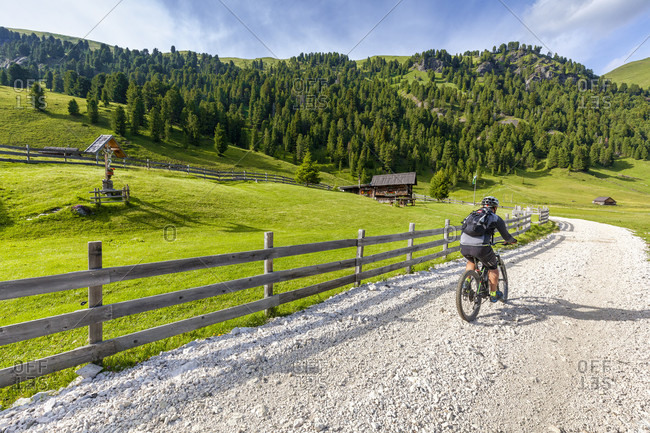 June 21, 2020: Cyclist with an electric mountain bike (e-bike) pedaling in Duron valley, Fassa Valley, Campitello di Fassa, Trento, Dolomites, Italy