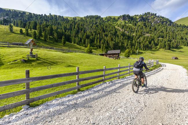 June 21, 2020: Cyclist with an electric mountain bike (e-bike) pedaling in Duron valley, Fassa Valley, Campitello di Fassa, Trento, Dolomites, Italy