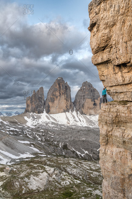 Drei Zinnen, Dolomites, Bolzano province, South Tyrol, Italy. A mountain climber admires the mountain panorama on an exposed rock band