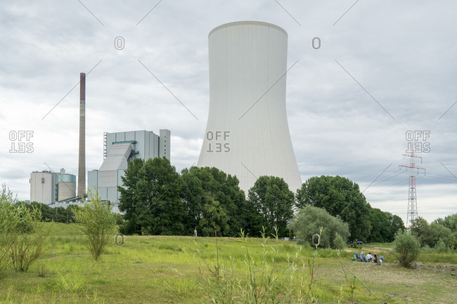 Rhine bank near Rhine ferry Walsum, picnic in front of industrial plant with cooling tower, contrast between people and industry