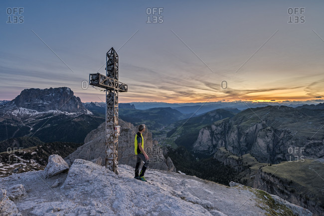 Gardena Pass, Bolzano Province, South Tyrol, Italy. A mountaineer at the summit of the Grosse Cirspitze admires the sunset