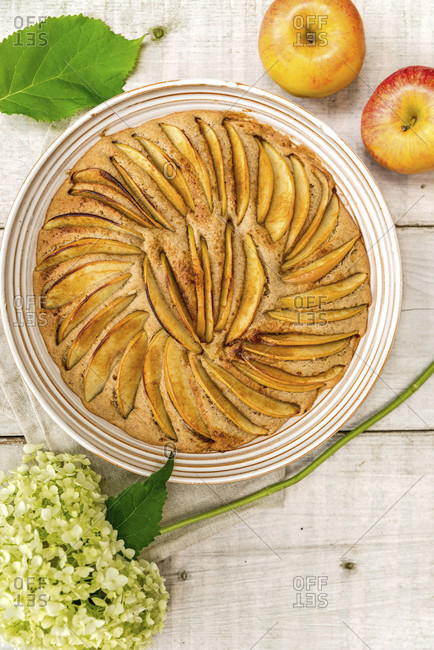 Apple pie baked in a round shape and decorated with apple slices, decorated with two apples and a white hydrangea flower