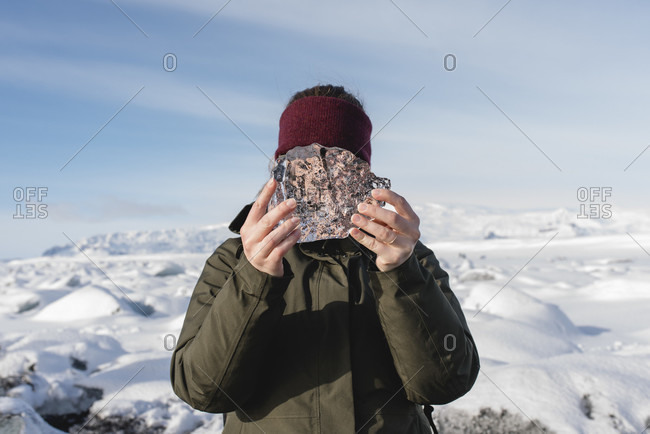 Woman holds small piece of ice in front of her face, Black Diamond Beach with its eponymous ice formations, Iceland