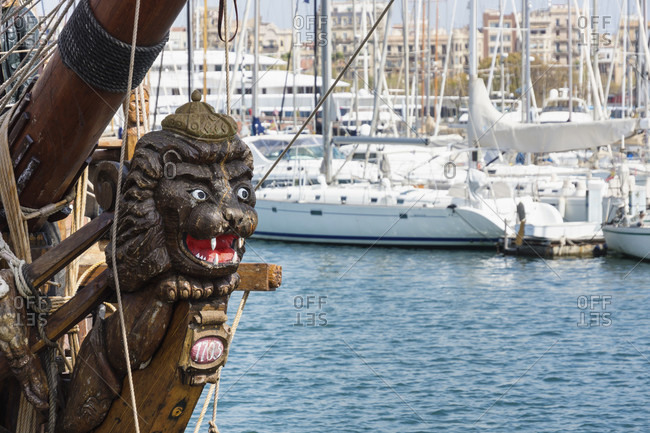 March 31, 2016: Barcelona, Port Vell, old port, historic sailing ship, figurehead, behind it modern yachts
