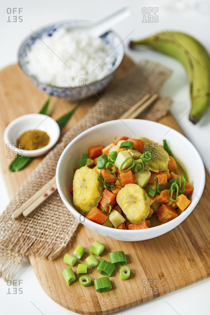 Asian curry with plantain and a bowl of white rice on wooden board with chopsticks and decoration