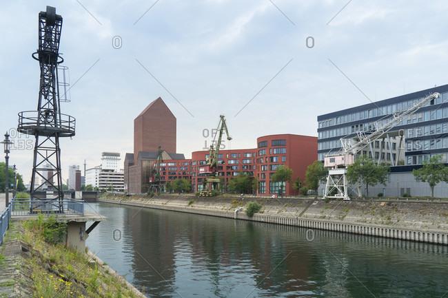 June 11, 2020: Duisburg, inner harbor, harbor promenade, warehouse and historic cranes