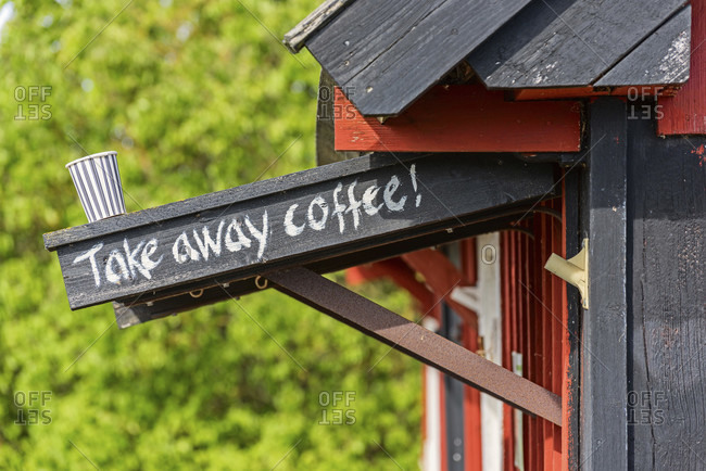 Coffee mug stands on canopy with take away coffee lettering, wooden house in the gate
