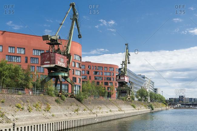 June 11, 2020: Duisburg, inner harbor, modern office buildings and historic cranes