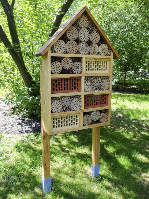 Insect hotel on stilts made of drilled wood, perforated stones and branches