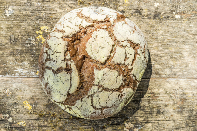 Round, freshly baked loaf of bread from above, weathered wood background