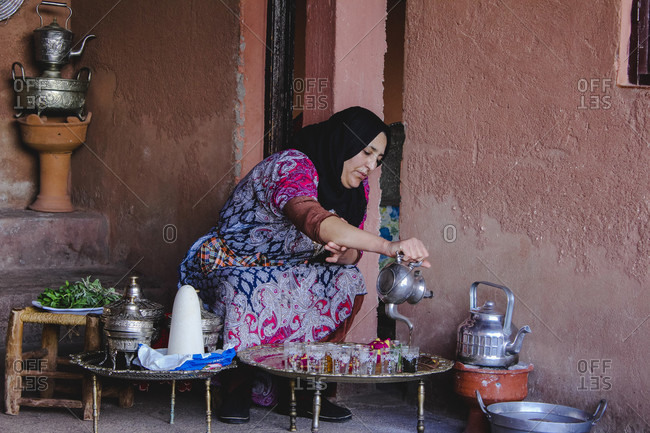January 25, 2018: Berber woman brewing and pouring Moroccan mint tea