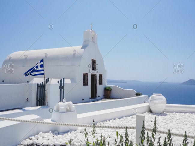 White church in Oia Santorini with Greek flag