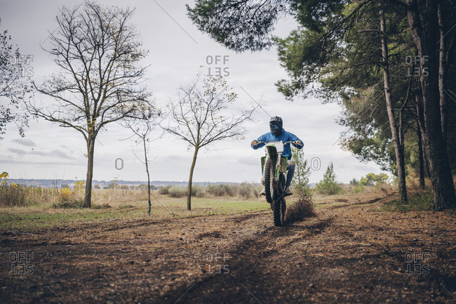 Teenage male rider performing wheelie on dirt road in forest