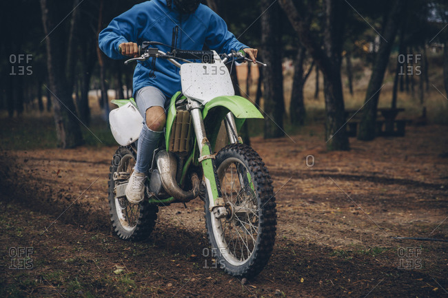 Teenage male rider riding on dirt track at forest during autumn
