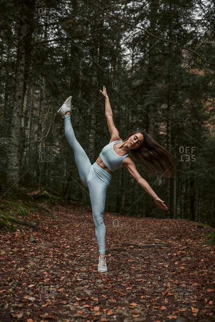 Woman with arms outstretched practicing rhythmic gymnastics in forest