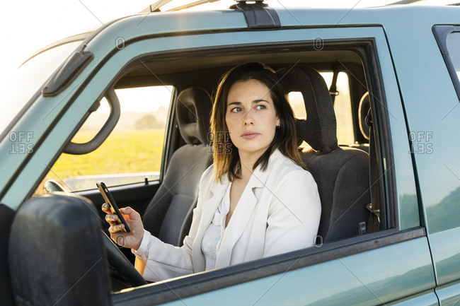 Young woman looking through window while holding mobile phone in car during road trip