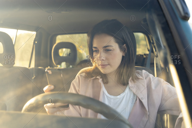 Young woman using smart phone while sitting in car during road trip at sunset