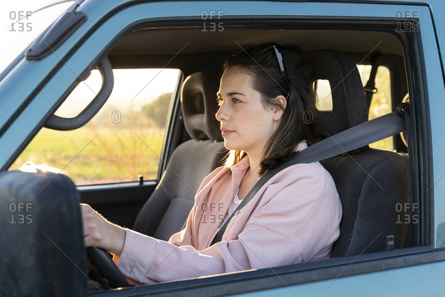 Young woman driving car on road trip