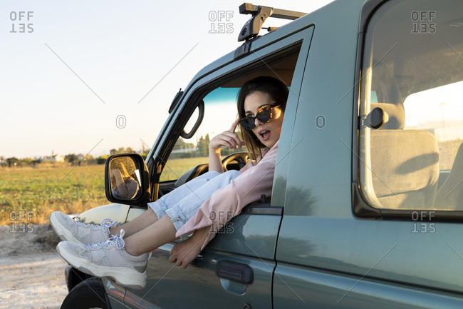 Surprised young woman looking away with feet up on car window during road trip at sunset