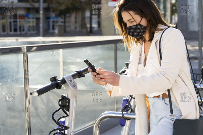 Young female entrepreneur doing contactless payment while standing at bicycle parking station