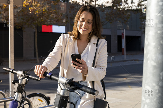 Smiling businesswoman doing contactless payment while standing at bicycle parking station
