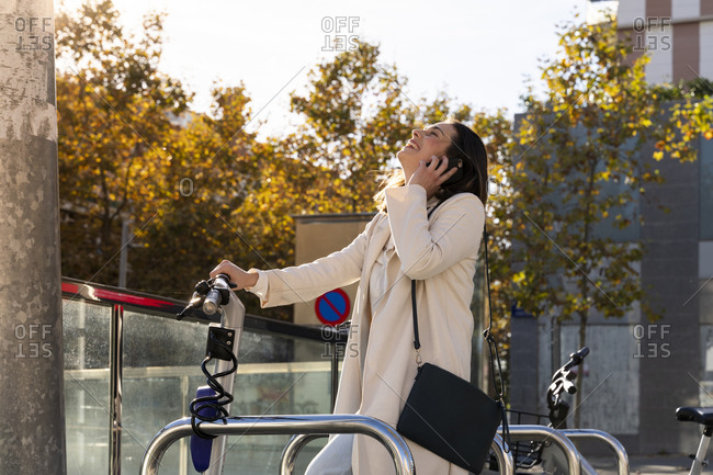 Female entrepreneur laughing while standing at bicycle sharing station